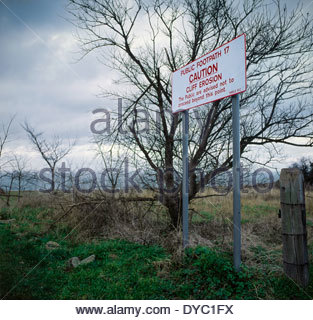 Sign warning of cliff erosion on footpath running close to clay cliffs on the North Kent coast - Stock Image