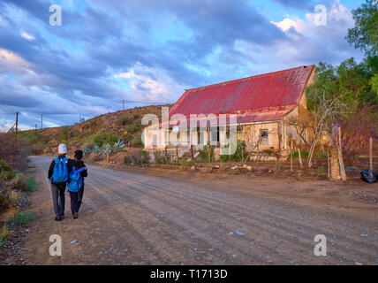 Karoo dirt road leading to a bend in morning light. Two teenagers  seen from back walking to school, passing ancient farm house - Stock Image