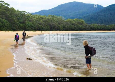 Three hikers walking along the deserted beach at Sealers Cove, Wilson's Prom, Australia. - Stock Image