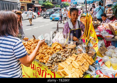 Bangkok, Thailand - April 21st 2011: Customer buying snacks from a street food vendor. Chinatown is full of food carts. - Stock Image