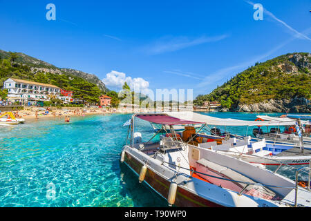 Tourists relax in the clear blue and turquoise waters and on the sandy Palaiokastritsa beach on the Aegean island of Corfu, Greece. - Stock Image