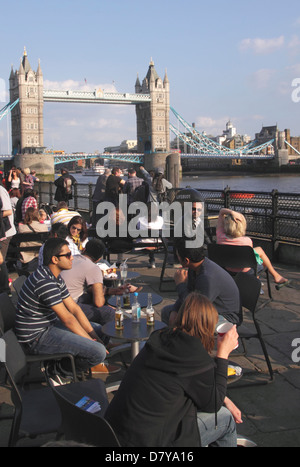 People drinking by the Tower Millennium Pier and Tower Bridge London - Stock Image