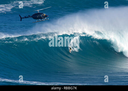 Helicopter and tow-in surfing action at Peahi or Jaws , Maui, Hawaii. - Stock Image