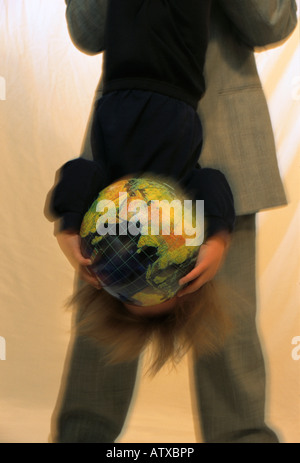 32 year old father holding 3 year old son upside down while the boy holds a globe in front of his face - Stock Image
