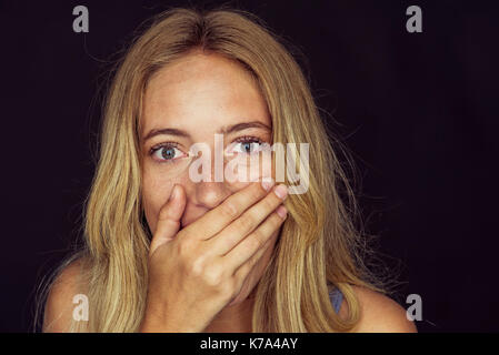 Young woman with wide eyes and hand covering mouth - Stock Image