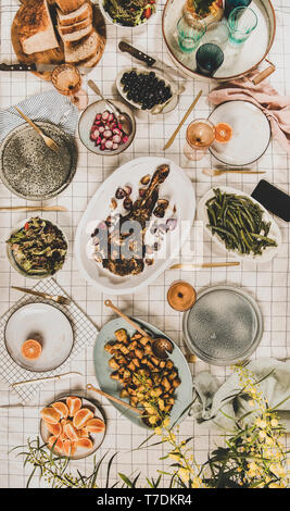 Family, friends gathering dinner. Flat-lay of roasted lamb shoulder, salads, baked vegetables, snacks, bread, rose wine and blooming mimosa branches o - Stock Image