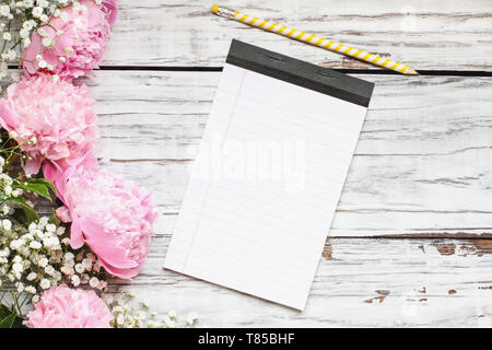 Pink Peonies and Baby's Breath flowers with pensil and blank note book over a white rustic wood table background  with copy space for your text. Flat  - Stock Image