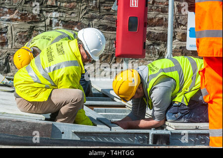 Schull, West Cork, Ireland. 16th Apr, 2019. West Cork Civil Engineering were given the task of refloating the €600,000 Schull pontoon, ready for the season.  Workers are seen preparing a piece of the pontoon onto the slipway, ready to be floated into the water. Credit: Andy Gibson/Alamy Live News. - Stock Image