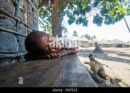 A child asleep on a bench on Baki island, the Turtle Islands, Sierra Leone. - Stock Image