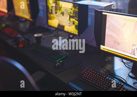 Close-up of computer monitors with arcade game pictures place on table with colorful keyboards in video game club - Stock Image