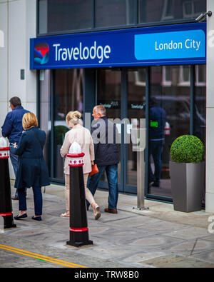 Travelodge London City - pedestrians walk past the entrance to the London City Travelodge hotel - Stock Image