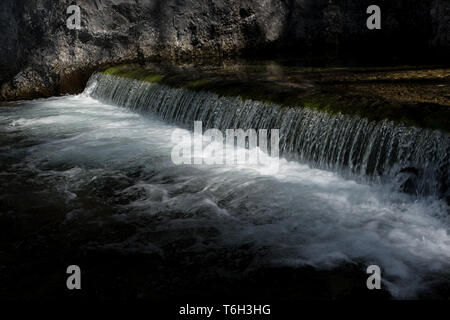 Sunlit Waterfall With Fresh Water Of An Alpine River - Stock Image