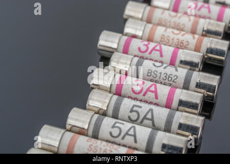 Domestic appliance 3A, 5A & 13A electrical fuses (Ceramic Cartridge type) on reflective black background. Metaphor electrical safety. 25mm L x 6.3mm D - Stock Image