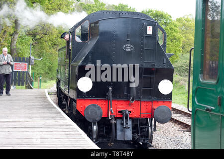 Locomotive 41313 on the Isle of Wight steam railway approaching carriages ready for coupling watched by a photographer - Stock Image