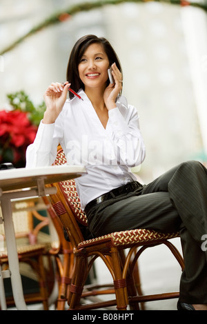 A young woman is sitting at a table seemingly chatting on the phone. - Stock Image