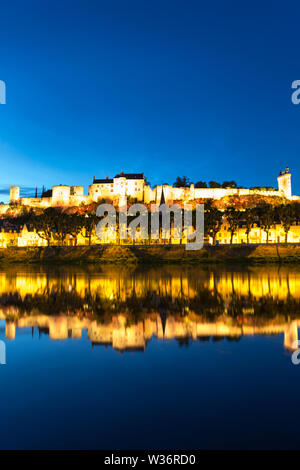 Chinon, France. Picturesque evening view of the River Vienne at Chinon, with the floodlit Forteresse Royal and Fort Saint George in the background. - Stock Image