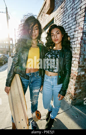 Two young smiling women with long curly black hair standing on pavement, holding skateboard, looking at camera. - Stock Image