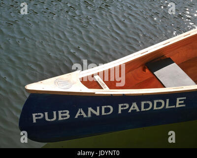 Detail of Wooden Canoe available of hire moored on the Norfolk Broads with words 'Pub and Paddle' on the - Stock Image