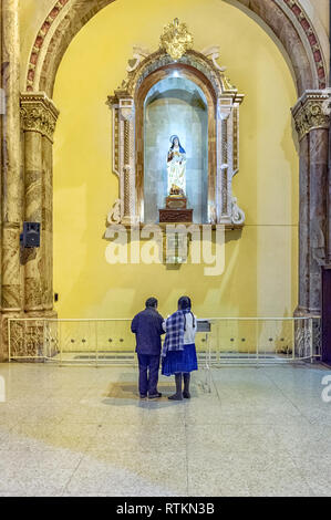 South American indigenous couple at the shrine of Saint Teresa, The Cathedral of the Immaculate Conception, aka the New Cathedral. Cuenca Ecuador - Stock Image