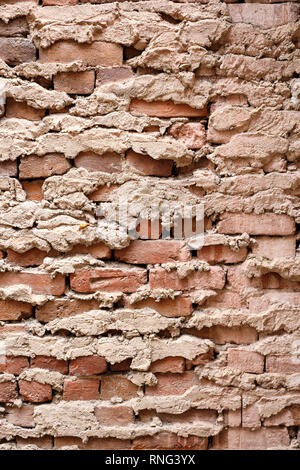 Old weathered cracked and damaged brick background in a pattern with heavy texture and different colors. - Stock Image