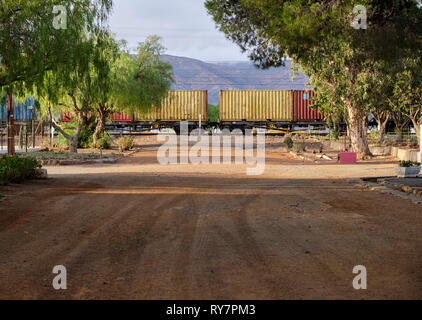 Cargo train with containers at railroad crossing on dirt road, in Great Karoo, South Africa - Stock Image