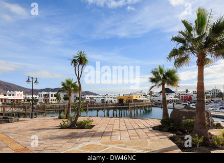 Seafront promenade in coastal resort of Marina Rubicon, Playa Blanca, Lanzarote, Canary Islands, Spain - Stock Image
