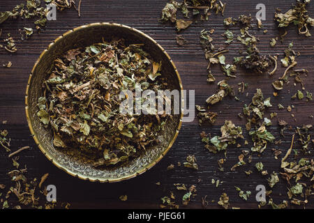 Brass Bowl of Dried Patchouli on Wood Table - Stock Image