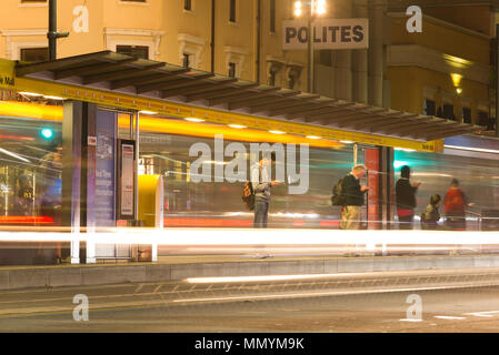 Individuals wait for a tram in King William Street, Adelaide at night in South Australia, Australia. - Stock Image