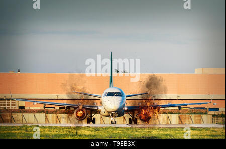 Front view of airplane with twin engines on fire on tarmac - accident or terrorism concept - Stock Image