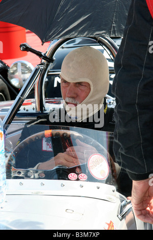 Racing driver in a classic racing car geting ready to put on his helmet in the pit lane at Silverstone - Stock Image