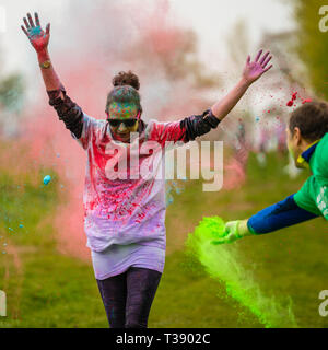 Adult female runner with arms held high being covered in paint on Macmillan cancer charity 5K color fun run. - Stock Image