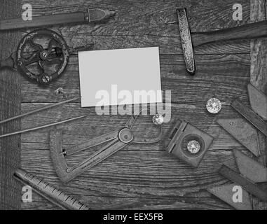 black and white image of a vintage jeweler tools and diamonds over wooden bench, space for text on a blank businesscard - Stock Image