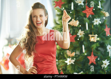 smiling modern woman in red dress fingers snapping near Christmas tree - Stock Image