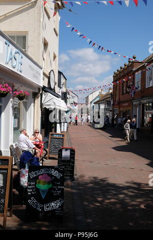Shoppers shop at Sidmouth Fore Street, Devon, UK - Stock Image