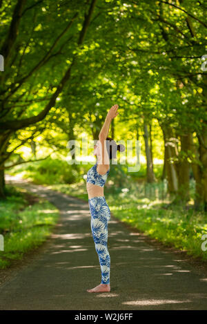 woman practicing yoga and meditation in the shade of trees. - Stock Image