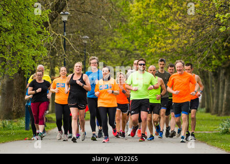 Adults Keeping fit : A group pf people in bright flourescent lycra running jogging exercising outdoors  in the park on a warm spring evening, Aberystwyth Wales UK - Stock Image