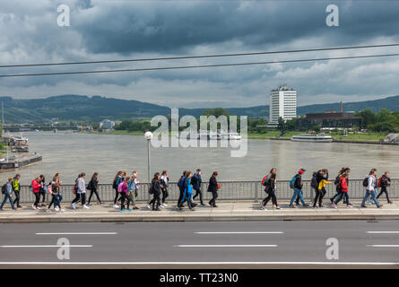 Linz Nibelungen Bridge across the river Danube with students, river cruise boats and Arcotel Nike. Nibelungenbrücke Linz Österreich Austria. - Stock Image