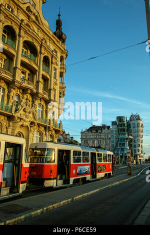 Tram ( Trolley ) travelling through the city of Prague with the Dancing House ( Tančící dům ) in the blue skied background. Prague, Czech Republic. - Stock Image