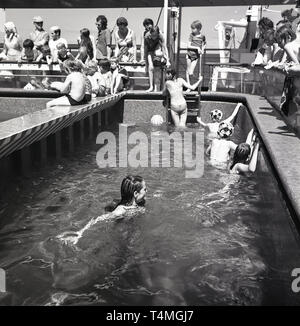 1960s, youngsters playing in the childrens section of the ship's open-air swimming pool. - Stock Image