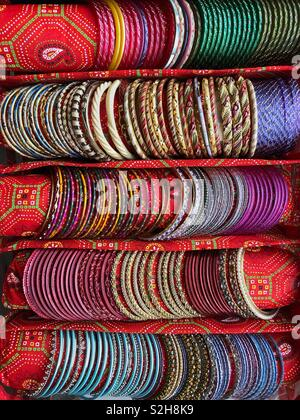 Rows of colourful Indian bangles on display in a specially made carry case. - Stock Image