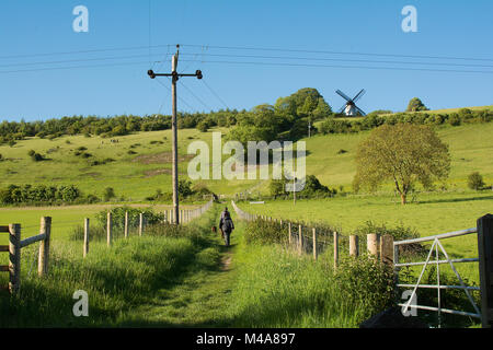 English country landscape with people walking dogs and a windmill on the horizon © Jeremy Graham-Cumming - Stock Image