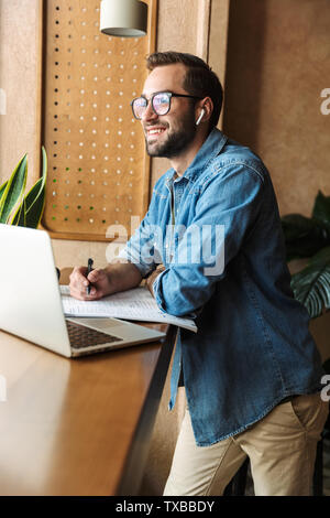 Photo of brunette happy man wearing glasses writing and using earpod with laptop while working in cafe indoors - Stock Image