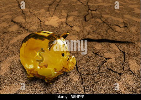An empty golden piggy bank stands in a parched desert landscape. - Stock Image