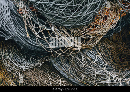 A heap of commercial fishing nets on the quayside. - Stock Image
