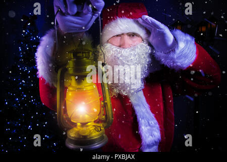 Young santa clause, carrying lantern looking through blizard of wind and snow - Stock Image
