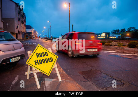 Bantry, West Cork, Ireland. 12th Oct, 2018. A car passes a 'Road Flooded' sign in Bantry early this morning after a night of heavy rain and winds which has left 30,000 homes around Ireland without power.  The storm is tracking northwards and will fizzle out by 5pm this evening. Credit: Andy Gibson/Alamy Live News. - Stock Image