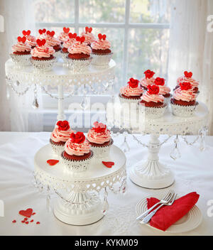Cupcakes. Red velvet cupcakes decorated with red roses and hearts on 3 tier cakestand. - Stock Image