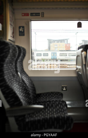 Two empty airline style seats on an Abellio Greater Anglia train,while on a platform - Stock Image