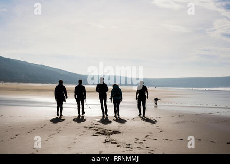 A group of people walking on a quiet sandy beach at low tide. Woolacombe, North Devon, England, UK, Britain - Stock Image