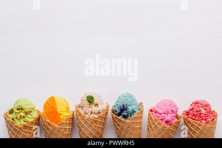 Various of ice cream flavor in cones blueberry ,strawberry ,pistachio ,almond ,orange and cherry setup on white wooden background . Summer and Sweet m - Stock Image